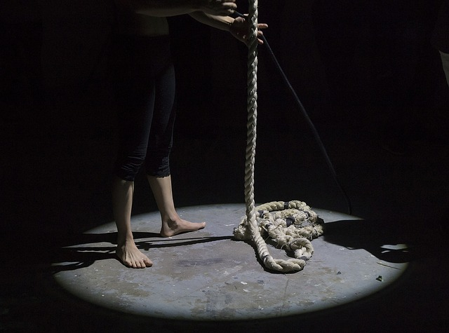 Person in spotlight on stage with rope